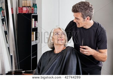 Happy female client and hairdresser looking at each other in beauty salon