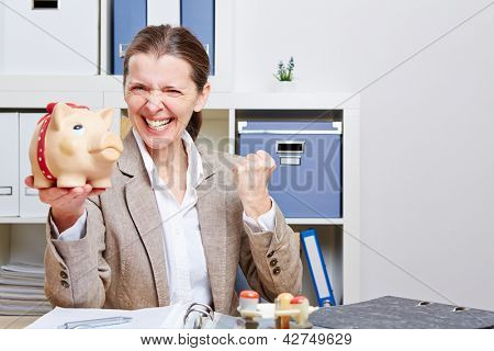 Successful senior business woman with piggy bank cheering in her office