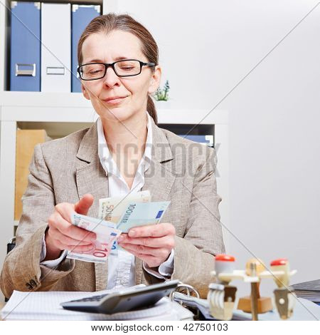 Senior accountant counting Euro money bills in her office