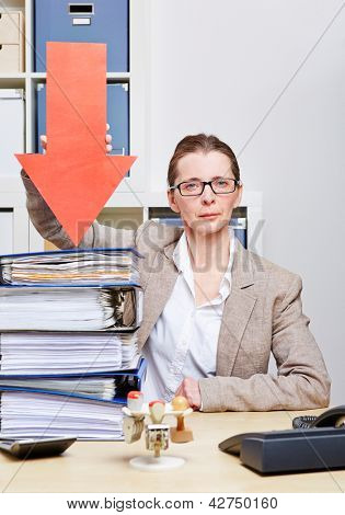 Strict business woman in her office pointing arrow to stack of files