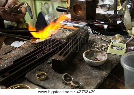 Jeweler melting silver in crucible with gasoline burner for making jewelry