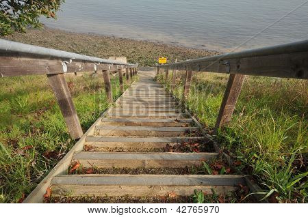 Steps With Railings Lead Down To A Beach