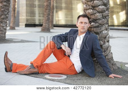 Handsome man sitting by a tree