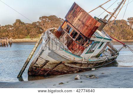 Shipwreck Awash On Beach