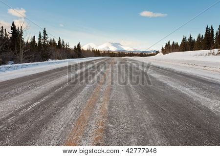 Winter on country road in taiga and snowy mountain