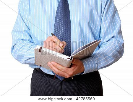 Businessman In Blue Shirt With Notebook And Pen Writes