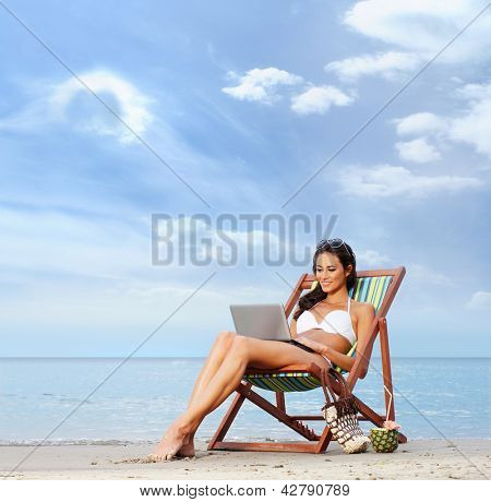 Young, beautiful, sporty and sexy woman with the notebook pc relaxing on the beach