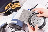 Close up of an airplane pilot hand holding flight computer and making pre-flight calculations with e