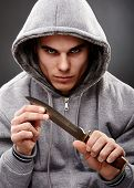 stock photo of thug  - Closeup portrait of a threatening mafia man holding a knife in his hands over gray background representing the concept of danger - JPG