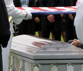 stock photo of funeral  - Funeral at Arlington National Cemetery with flag over casket with reflections - JPG