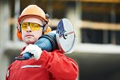 picture of millwright  - builder worker in safety protective equipment with grinding machine power tool at construction site - JPG