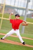 foto of little-league  - Little league pitcher in red jersey in the middle of his pitch making a funny face - JPG