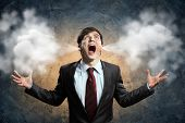 image of pressure  - businessman in anger screaming puff going out from ears - JPG