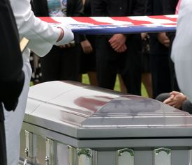 picture of funeral  - Funeral at Arlington National Cemetery with flag over casket with reflections - JPG