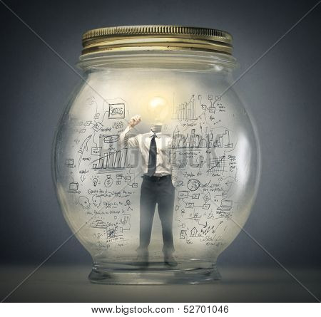 businessman writing with the head in the shape of a light bulb enclosed in a jar