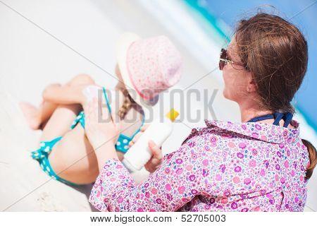 Mother applying sunblock cream on her daughters shoulder