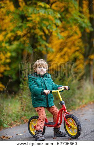 Cute Preschool Boy Of Three Years Riding Bike In Autumn Forest