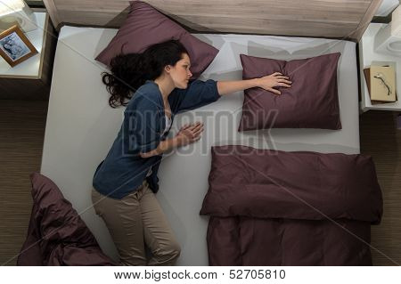 Young widow lying in bed missing her husband
