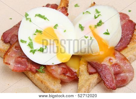 Two poached eggs with bacon on toast cooked breakfast.