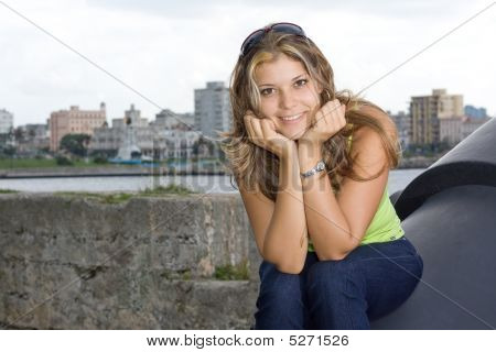 Beautiful Lady Smiling And Siiting On An Old Cannon
