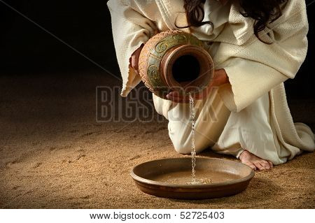 Jesus pouring water from jug to pan to wash feet of disciples