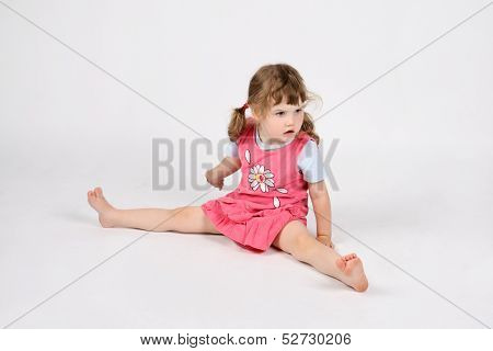 Little Surprised Barefoot Girl In Pink Sits On Floor And Looks Away On White Background.