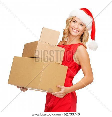 christmas, x-mas, winter, happiness concept - smiling blonde woman in santa helper hat with many parcel boxes