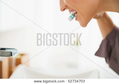 Closeup On Happy Woman Brushing Teeth In Bathroom