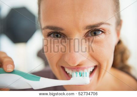 Smiling Young Woman Brushing Teeth In Bathroom