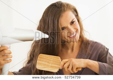 Happy Young Woman Brushing And Blow Drying Hair In Bathroom