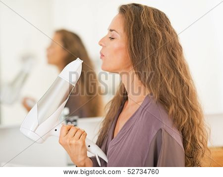 Happy Young Woman Blowing On Blow Dryer