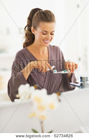 Happy Young Woman Squeezing Toothpaste From Tube