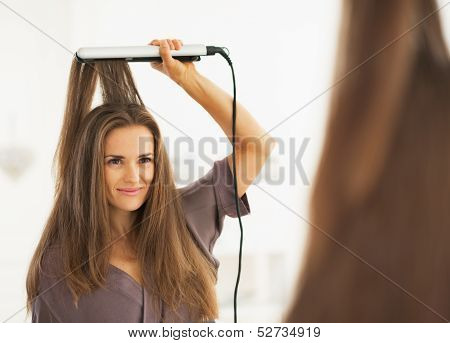 Portrait Of Woman Straightening Hair With Straightener