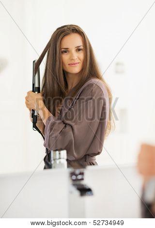 Woman Straightening Hair With Straightener
