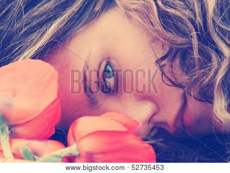 a girl resting her head on a table with flowers vintage toned