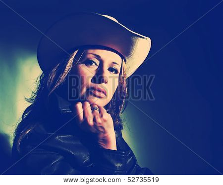 a studio shot of a cowgirl with dramatic lighting vintage toned
