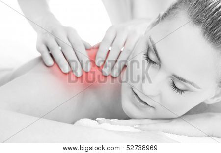 Woman getting massaging treatment over white background (black and white image with the red inflammation area)