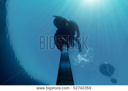 Freediver Holding His Breath Deap In The Water With Beams Of Light Above Him.