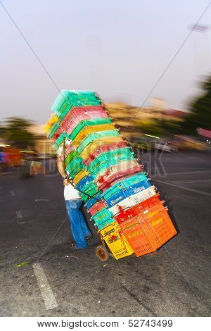 Man Carries Plastic Crates On A Sack Barrow