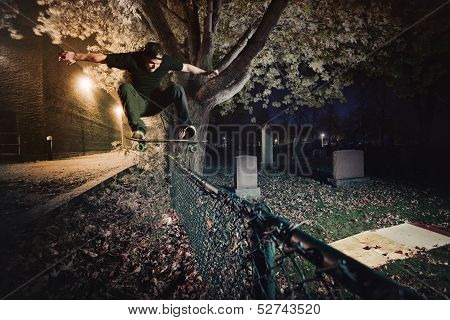 Skateboarder Doing A Ollie Trick Over A Fence At Night