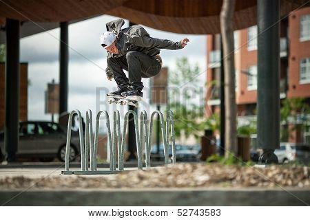 Skateboarder Doing A Ollie Over A Bike Rack