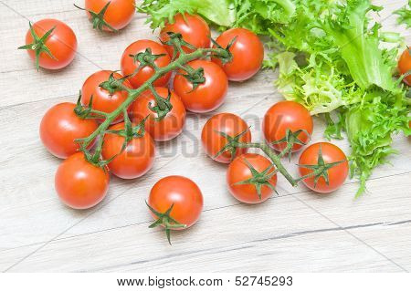 Ripe Cherry Tomatoes And Salad Frieze On A Wooden Table