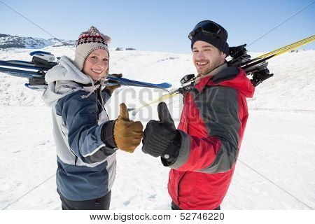Rear view portrait of a smiling couple with ski boards gesturing thumbs up on snow covered landscape