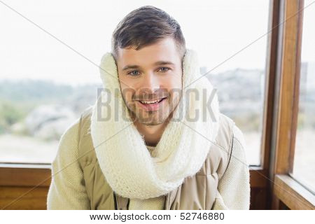 Portrait of a smiling young man wearing earmuff while sitting against cabin window