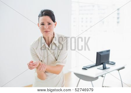 Portrait of a young businesswoman suffering from wrist pain in the office