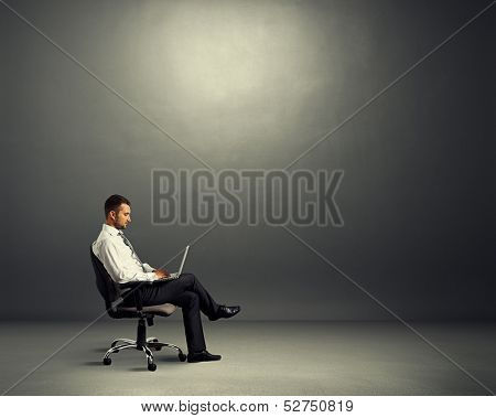 concentrated young businessman sitting in empty dark room and working with laptop