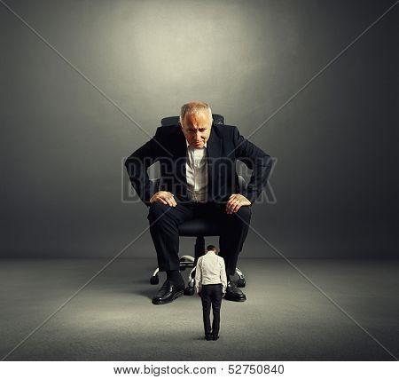 big boss looking at small bad worker