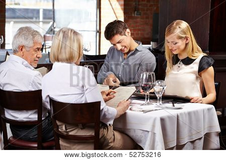 Family with in-laws in a restaurant reading the menu