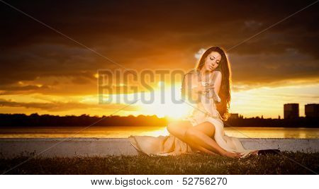 brunette Caucasian woman in dress posing provocatively outdoor in front of a beautiful sunset