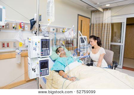 Worried young woman looking at critical patient in hospital